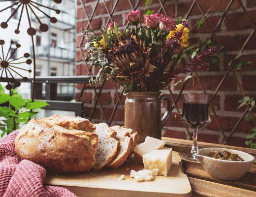 Ein Stillleben aus einem Trockenblumenstrauss, einem Brot, Käse, Wein und Oliven